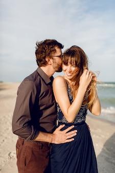 ロマンチックなカップルは海の近くの夕方のビーチを受け入れます。優しさと彼氏を抱き締める青いドレスのエレガントな女性。