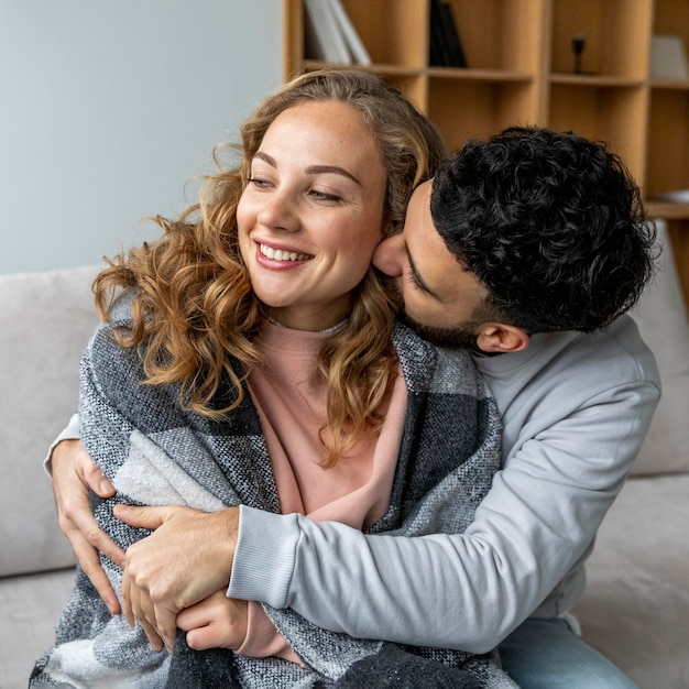 Romantic couple embraced on the couch at home