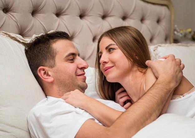 ロマンチックなカップルはベッドに抱かれ