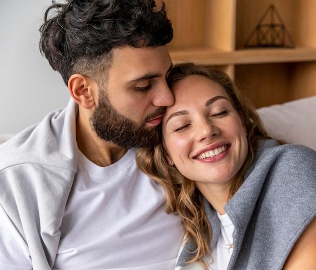 Coppia romantica abbracciata sul divano di casa