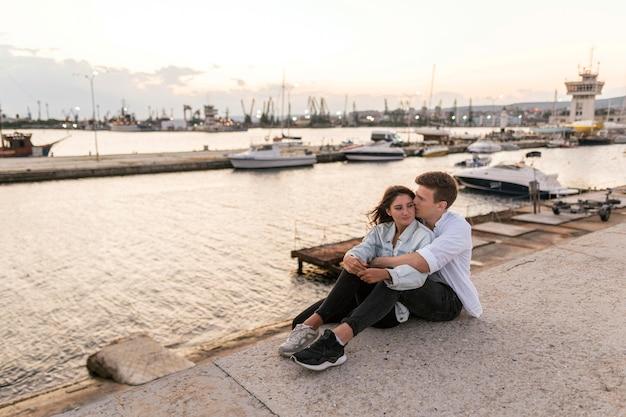 ロマンチックなカップルは港の屋外を包含します。