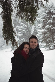 Romantic couple embracing in forest during winter