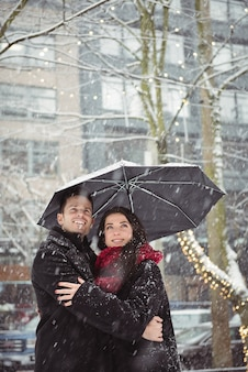 Romantic couple embracing in street during snowfall
