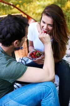 公園でピクニックを楽しんでいるロマンチックなカップル