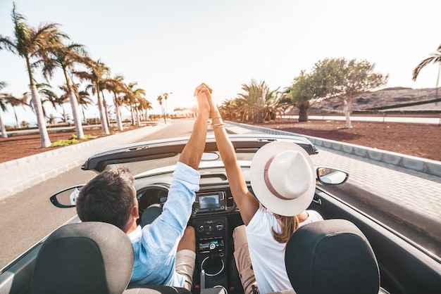 Romantic couple enjoying holidays driving a convertible car on the road at sunset.