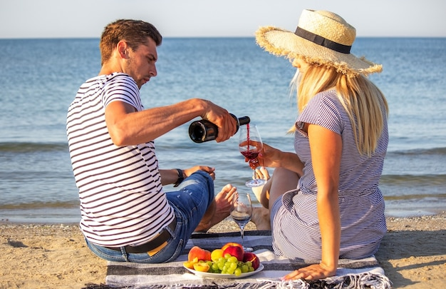 海のそばでワインを楽しむロマンチックなカップル。セレクティブフォーカス