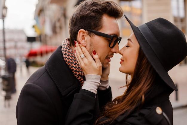 ロマンチックなカップルは、抱き合ったり笑ったりします。暖かく居心地の良い色、冬のムード。街を歩いているハンサムな男とエレガントな黒髪の女性。
