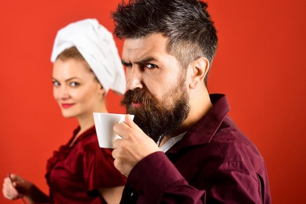 ロマンチックなカップル-ハンサムなひげを生やした夫はコーヒーを飲み、背景にぼやけた妻。カップルは家で朝食をとります。愛、ロマンチック、カップル、関係、愛情、ライフスタイルの概念。スペースをコピーします。
