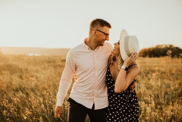 Romantic couple in hat walking in the meadow.