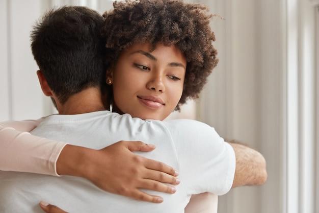 ロマンチックなカップルは屋内で暖かい抱擁を持っています