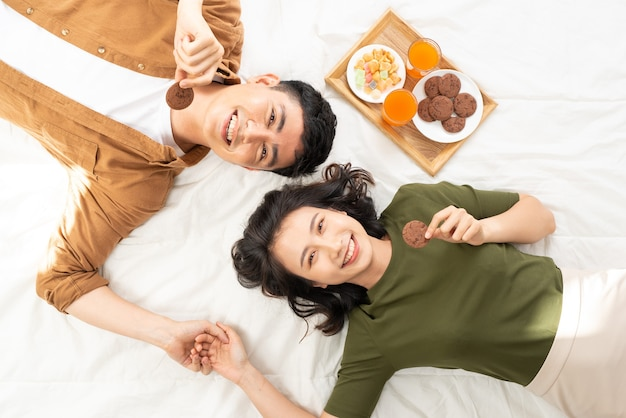 Romantic couple having breakfast lying in the bed at home