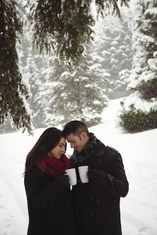 Romantic couple having cup of coffee in winter forest