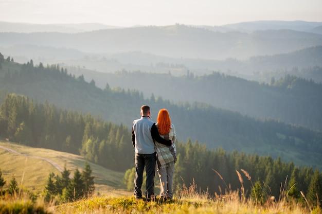 Romantic couple hikers on a hill, enjoying beautiful mountain landscape
