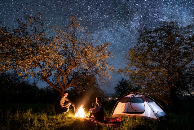 Romantic couple hikers sitting at a campfire near tent under trees and beautiful night sky full of stars and milky way