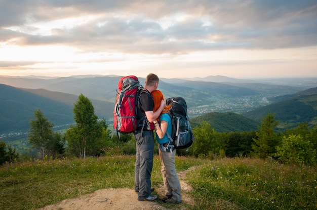 Romantic couple hikers with backpacks standing embracing and enjoying the view of beautiful open overlook on the mountains, forests, hills, village in the valley and cloudy sky