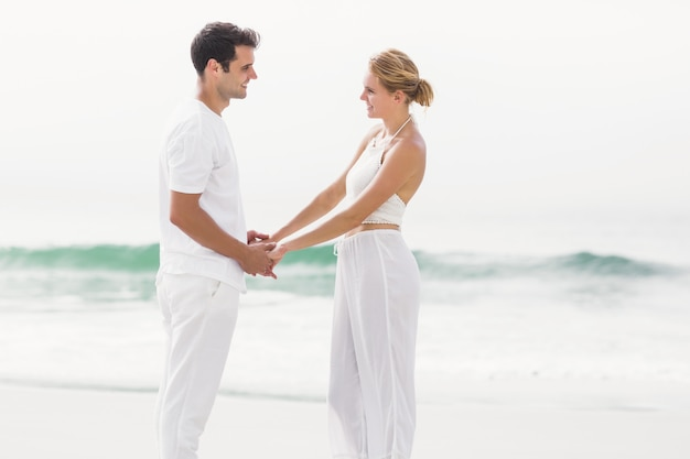 Romantic couple holding hands on the beach