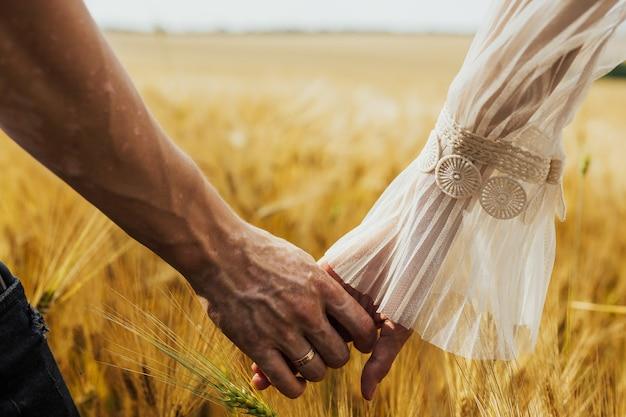 フィールドで手をつないでロマンチックなカップル。手をつないでフィールドを歩いている男性と女性のショットをクローズアップ。手に白斑を持つ男。
