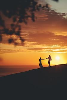 日没時に海の海岸で手をつないでロマンチックなカップル