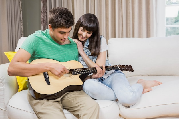Romantic couple at home playing guitar on the sofa in their living room