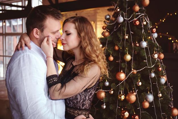 Романтическая пара обнимается возле елки