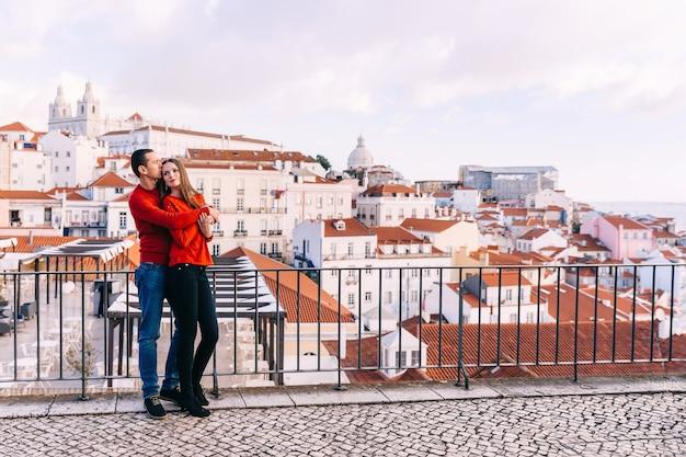 ロマンチックなカップルは、街のパノラマの背景に赤いセーターを抱きしめます。