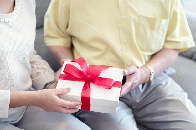 Romantic couple, husband holding surprise gift box for her wife sitting on couch together.