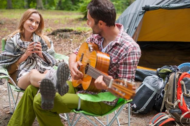 캠핑에서 로맨틱 커플입니다. 기타를 연주하는 남자.