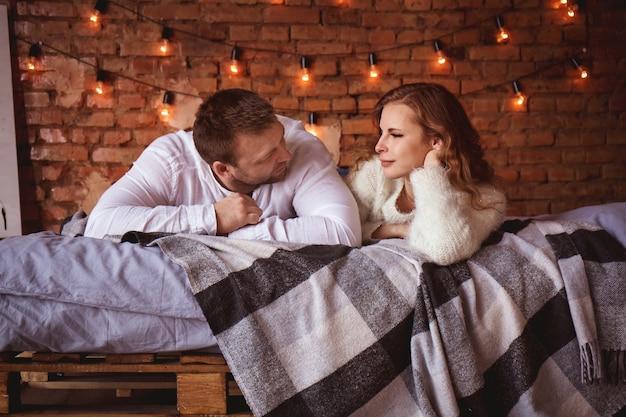 Романтическая пара в постели у кирпичной стены