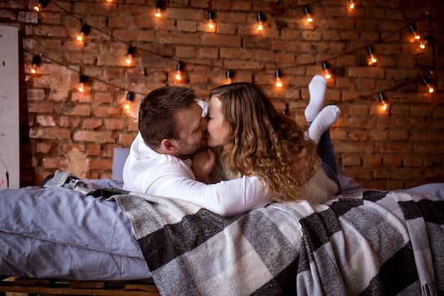 벽돌 벽에 침대에서 로맨틱 커플