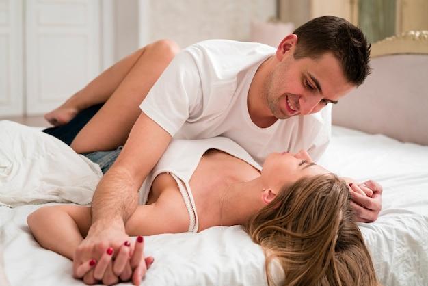 ベッドの笑顔でロマンチックなカップル