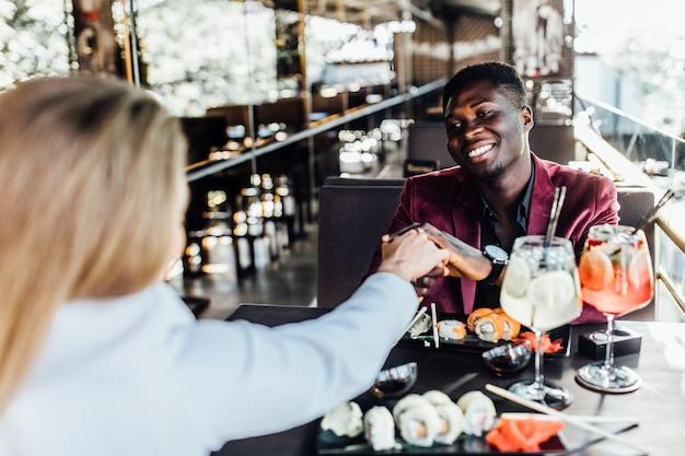 カフェのロマンチックなカップルは、寿司と一緒にモヒートを飲み、一緒にいるのを楽しんでいます。男性は女性の手を握っています。