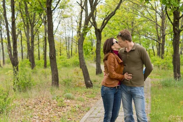 사랑에 빠진 로맨틱 커플은 삼림 지대의 돌길에 서서 부드러운 키스를 즐깁니다.