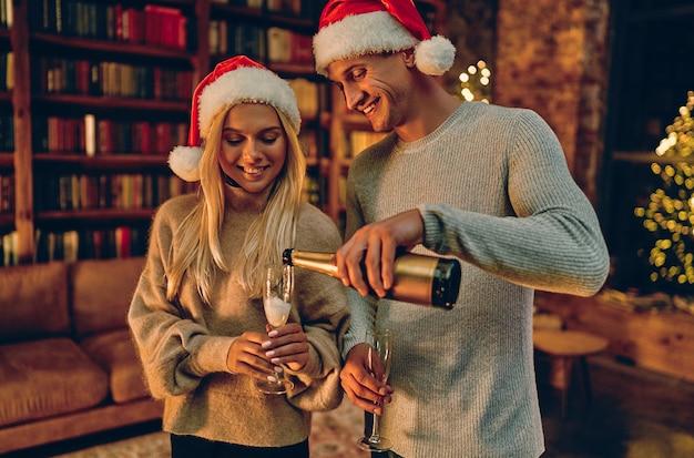 クリスマスや新年を一緒に過ごすロマンスに幸せを感じる恋愛中のロマンチックなカップル。男がグラスにシャンパンを注ぐ。