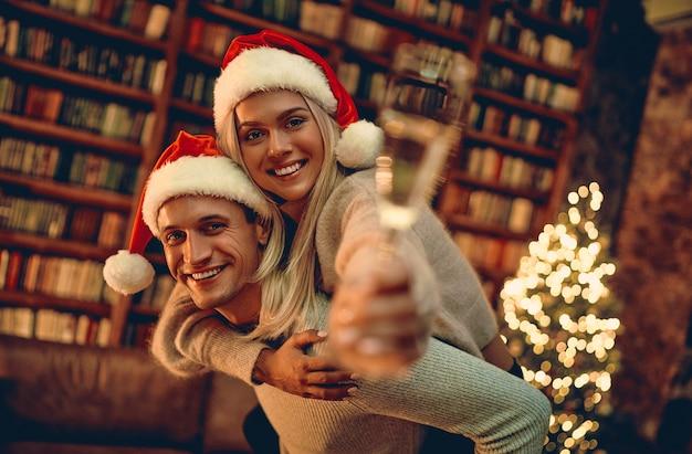 Романтическая влюбленная пара чувствует счастье от своего романа, проводящего вместе рождество или новый год. размытое изображение руки, держащей бокал шампанского.