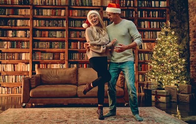 クリスマスや新年を一緒に過ごすロマンス、完璧な関係を楽しんでいる女性と男性、居心地の良い家のインテリアで冬の休暇を過ごすことについて幸せを感じている愛のロマンチックなカップル。