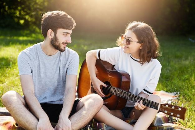Романтическая пара в любви, проводить время вместе, сидя на зеленой траве, играя на музыкальном инструменте. молодой бородатый мужчина с большой любовью смотрит на свою подругу, которая пытается играть на гитаре