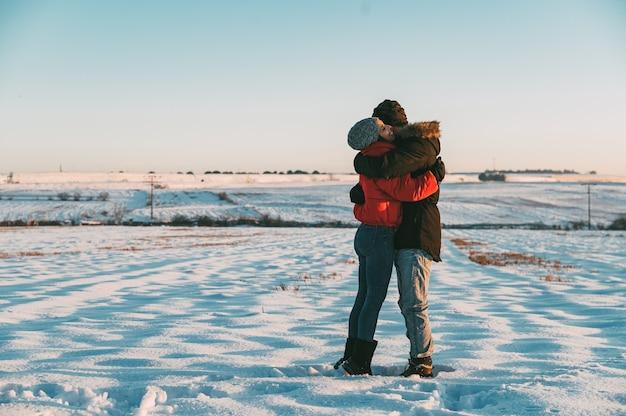 Романтическая влюбленная пара в теплой одежде, нежно обнимающаяся и целующаяся в заснеженной зимней сельской местности