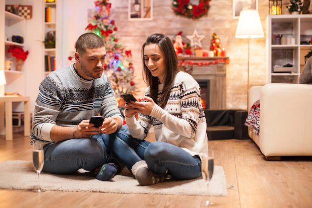크리스마스에 그들의 스마트 폰에서 온라인 쇼핑을 하 고 일치하는 옷에 로맨틱 커플.