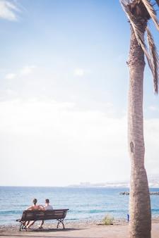 熱帯の夏休みの場所で地平線と海を見ている関係のロマンチックなカップル-リラックスして休日のコンセプトを楽しんでください