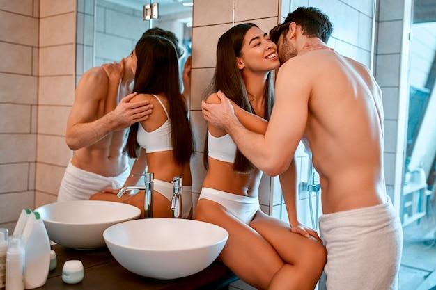 욕실에서 로맨틱 커플 포옹과 샤워 후 키스. 아침 루틴. 바디 케어.