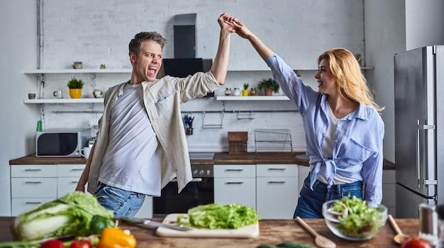 Романтическая пара готовит на кухне. красивый мужчина и привлекательная молодая женщина веселятся вместе, делая салат. концепция здорового образа жизни.