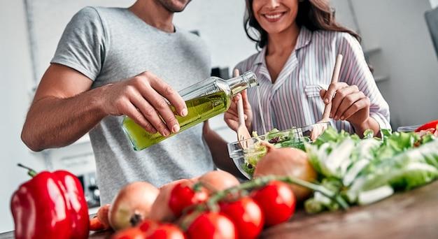 Романтическая пара готовит на кухне. красивый мужчина с бутылкой масла и привлекательная молодая женщина веселятся вместе, делая салат. концепция здорового образа жизни.