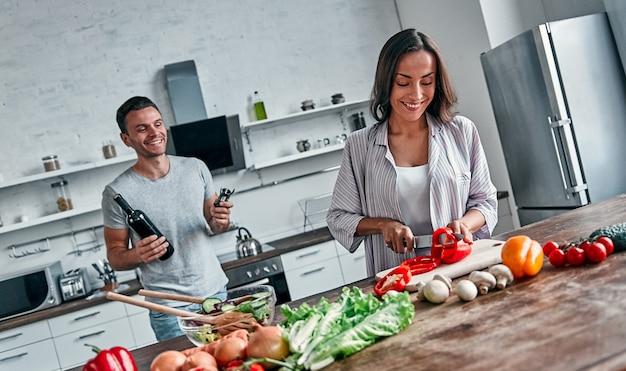 Романтическая пара готовит на кухне. красивый мужчина с бутылкой вина и привлекательная молодая женщина веселятся вместе, делая салат. концепция здорового образа жизни.