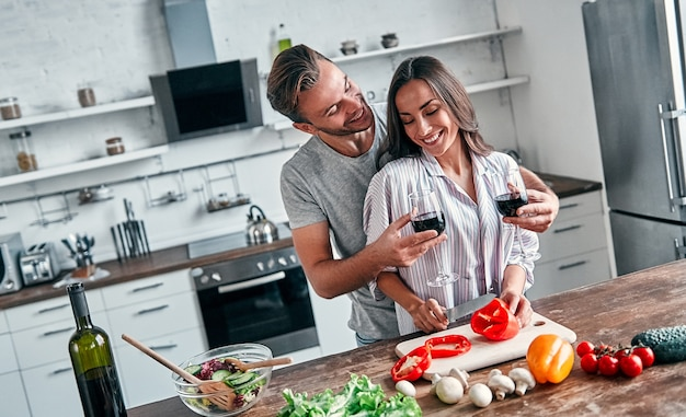 Романтическая пара готовит на кухне. красивый мужчина с бокалами вина и привлекательная молодая женщина веселятся вместе, делая салат. концепция здорового образа жизни.