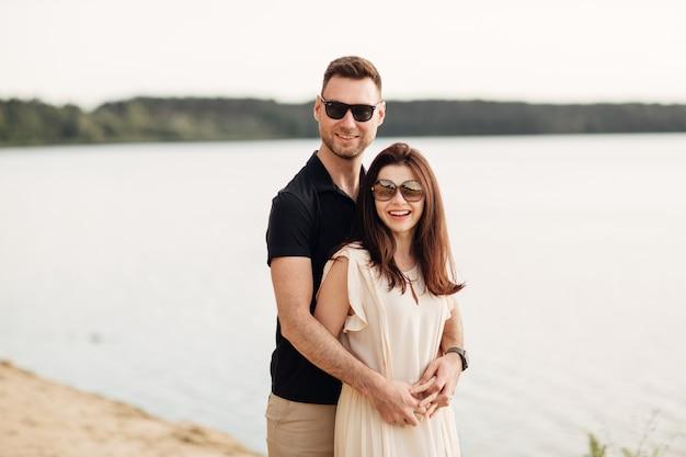 ロマンチックなカップルがビーチで抱き締めています
