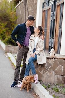 Романтическая пара гуляет по городу со своей собакой лабрадором
