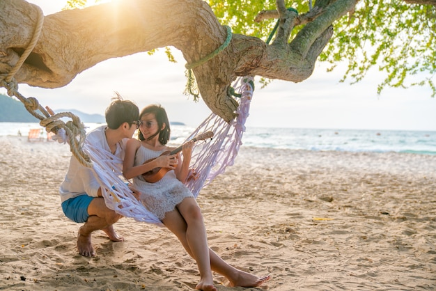 Romantic couple is sitting and kissing on sea beach on rope swing