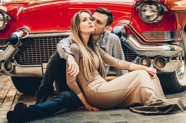 A romantic couple is sitting near red retro car.