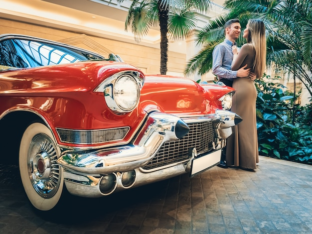 A romantic couple is standing by the red retro car.