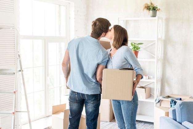 外に移動するために荷造りしながらロマンチックなカップルがお互いにキス